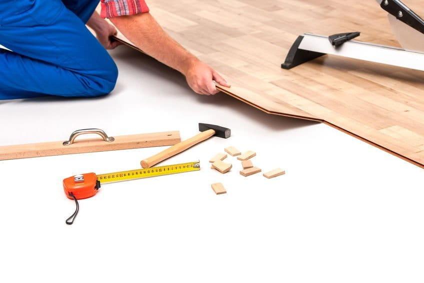 Ein Handwerker verlegt mit wenig Werkzeug Parkettdielen indem er sie ineinander steckt