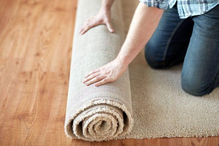 Ein Mann rollt einen Teppich auf einem Holzfußboden aus.
