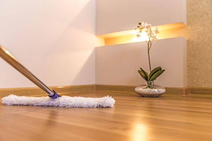 Reinigung eines Holzfußbodens mit einem weißen Wischmop