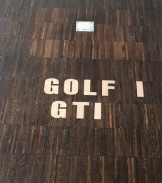 Buchstaben-Ausschnitte im Parkettboden
